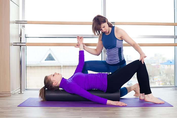 Woman stretching on gym mat - MFR Stretching - Monarch You