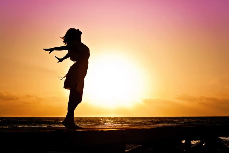 Woman silhouette against the sun on the beach monarch you physical therapy health