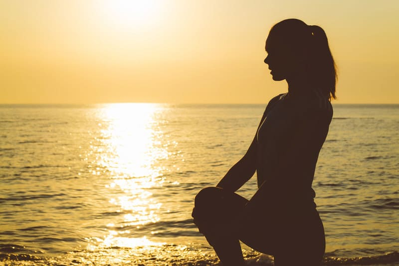Woman kneeling on sand in front of ocean and sunset Monarch You Physical Therapy