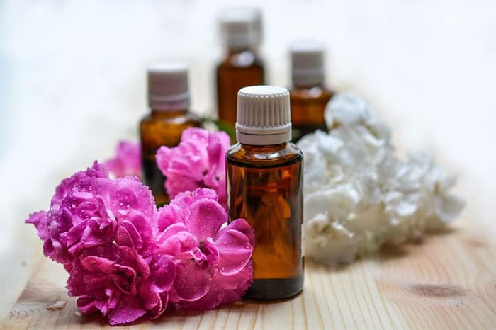Essential Oil Bottles with pink and white flowers - Young Living - Raindrop Technique